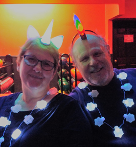 Theresa in unicorn headband, Mark with Christmas bulb mohawk and both wearing flashing snowflake necklaces.